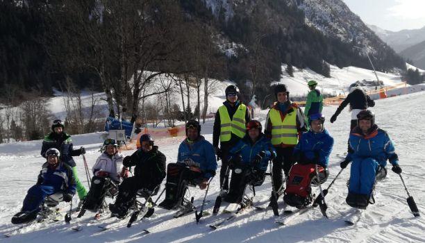 Sieben Monoskifahrer mit ihren Begleitpersonen